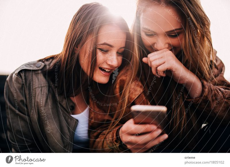 Happy Teenager girls using smart phone looking at pictures Human being Woman Youth (Young adults) Young woman Joy Girl 18 - 30 years Adults Natural Lifestyle