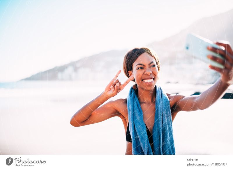 African young woman taking funny selfie with smartphone Human being Youth (Young adults) Young woman Ocean Joy Beach 18 - 30 years Adults Funny Sports Happy Rock Bright Technology Smiling Fitness
