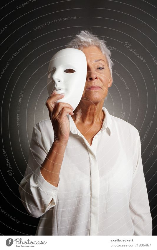 serious mature woman revealing face behind mask Human being Woman Old White Adults Emotions Senior citizen Playing Leisure and hobbies 60 years and older Female senior Mask Grandmother Hide Self-confident Identity