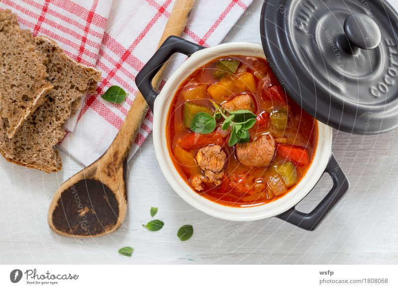 Goulash in a black cocotte with marjoram on white wood Bread Soup Stew Wooden spoon Dark Black White gulyas gollash gujash Marjoram Hungarian Eating Pepper