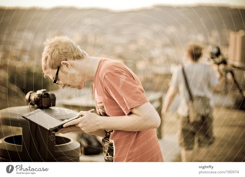 finding views Colour photo Subdued colour Exterior shot Evening Shallow depth of field Upper body Downward Notebook Camera Human being Man Adults 2