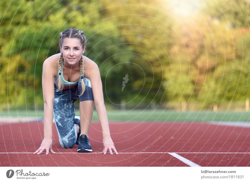 Athletic young woman in a starter position Happy Face Sports Racecourse Woman Adults 1 Human being 18 - 30 years Youth (Young adults) Blonde Fitness Smiling