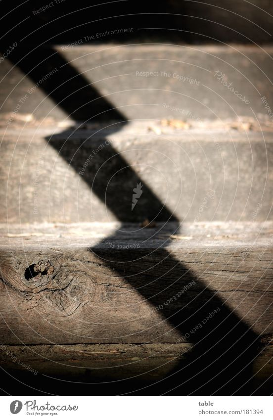 BY THE MIDDLE OF THE DAY. Colour photo Subdued colour Shadow Contrast Stairs Wood Sign Old Dark Sharp-edged Shaft of light Zigzag Upward Downward Knothole