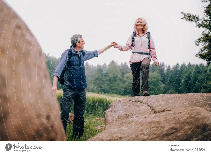 Senior Man helping his wife climbing up a rock on hike Woman Vacation & Travel Man Relaxation Joy Adults Senior citizen Sports Lifestyle Couple Together Tourism Leisure and hobbies Hiking Trip Action