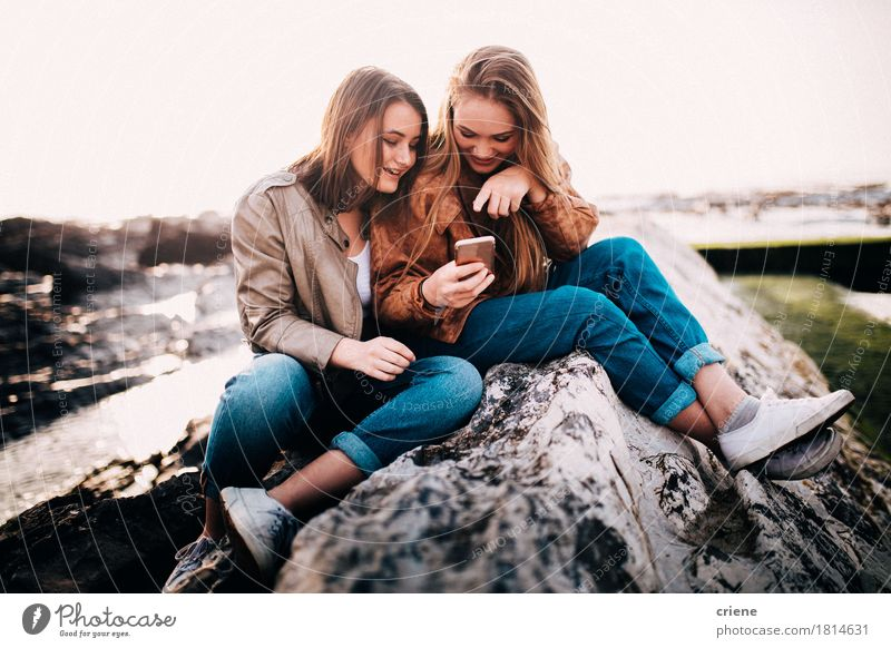 Happy Young teenager girls looking at smart phone Human being Woman Youth (Young adults) Young woman Ocean Joy Girl Beach Adults Emotions Lifestyle Laughter Happy Freedom Rock Together