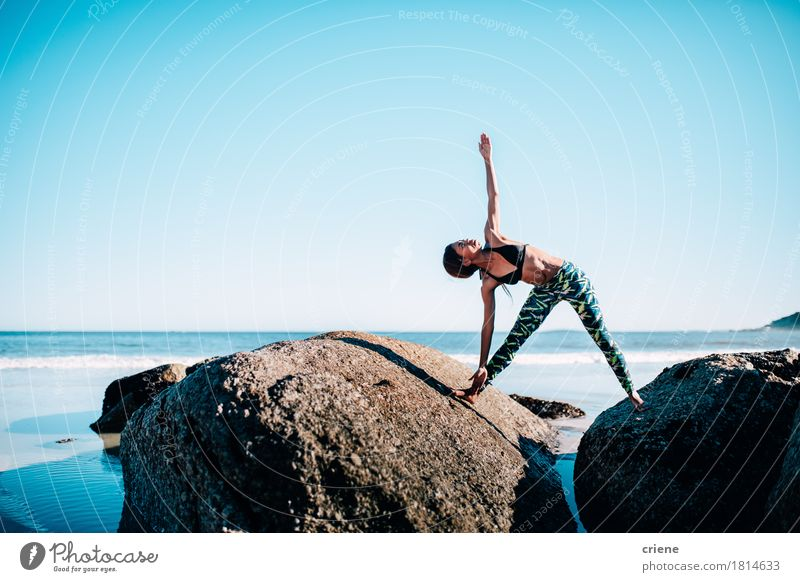 Fit African woman doing yoga exercise on rocks by the beach Human being Woman Youth (Young adults) Blue Young woman Water Ocean Relaxation Beach Adults Sports