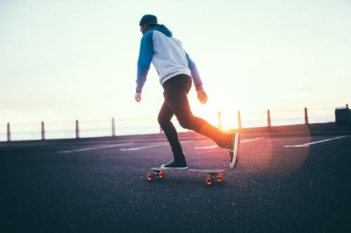 Hipster boy rolling with long board on promenade in sunset Human being Youth (Young adults) Man Young man Relaxation Adults Street Sports Lifestyle