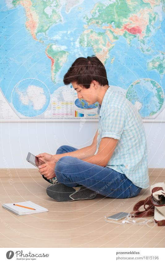 Boy sitting by the map in classroom Human being Youth (Young adults) Boy (child) School Think 13 - 18 years Study Academic studies Education University & College student Map Notebook Vertical Pencil Resolve Problem