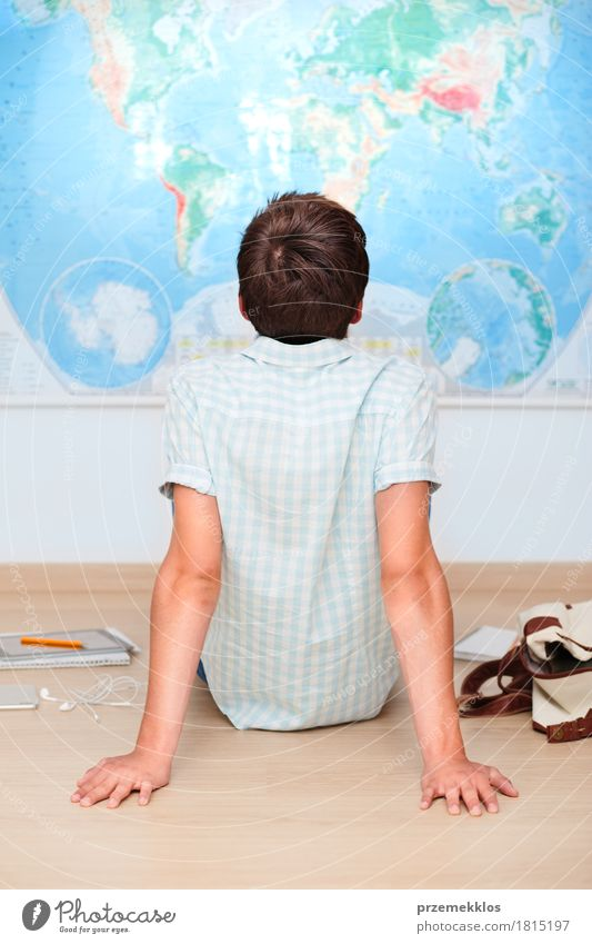 Boy sitting by the map in classroom Human being Youth (Young adults) Boy (child) School Think 13 - 18 years Study Academic studies Education University & College student Concentrate Map Vertical Pencil Resolve Problem