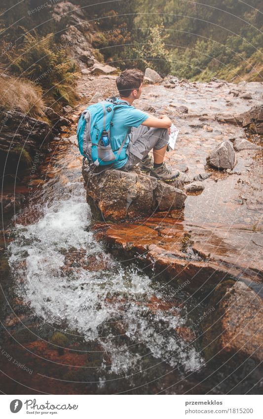 Boy sitting on a rock on mountain trail Human being Nature Vacation & Travel Youth (Young adults) Summer Water Relaxation Loneliness Mountain Lanes & trails