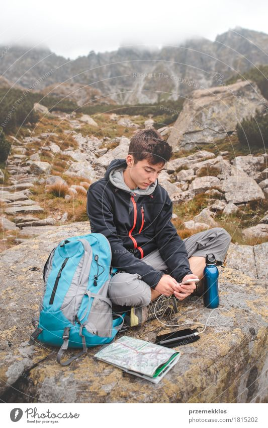 Boy resting on a rock and charging a mobile phone Bottle Lifestyle Leisure and hobbies Vacation & Travel Adventure Freedom Summer Mountain Hiking Human being