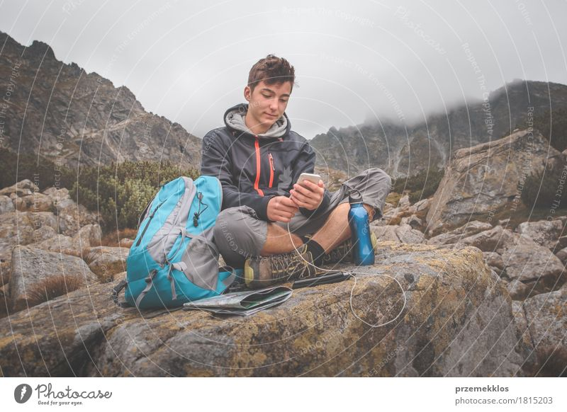 Boy resting on a rock and charging a mobile phone Human being Nature Vacation & Travel Youth (Young adults) Summer Mountain Lanes & trails Lifestyle Boy (child)