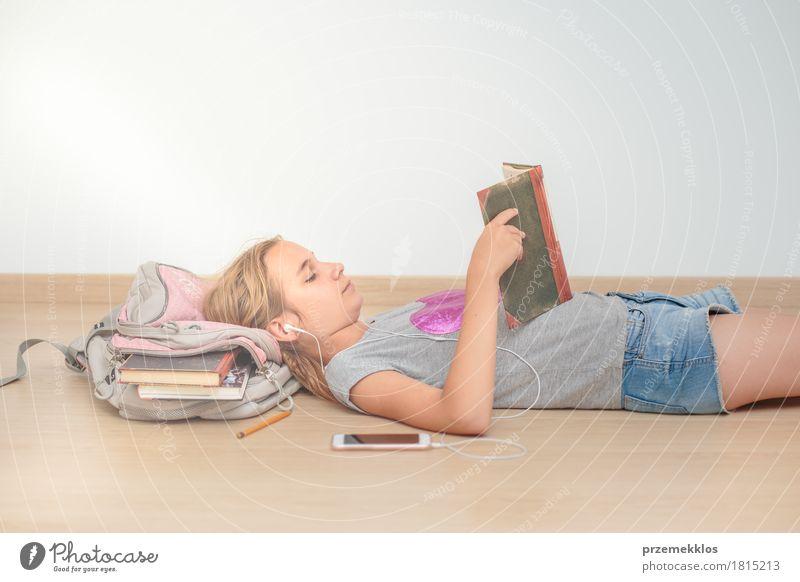 Schoolgirl reading a book in classroom Lifestyle Reading Education Classroom Schoolchild Academic studies University & College student Tool Girl