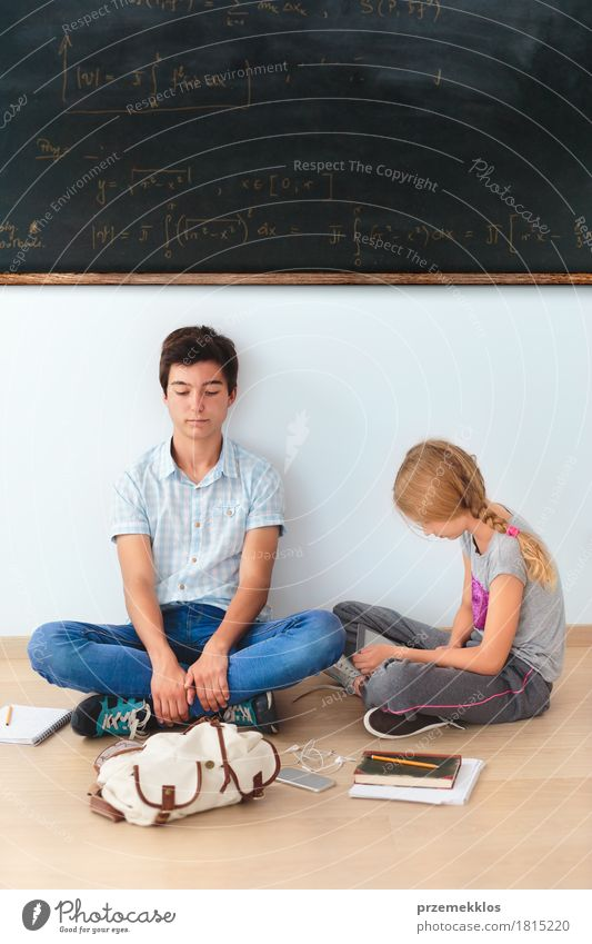 Teenagers sitting by a blackboard at school Human being Youth (Young adults) Girl To talk Boy (child) School Think 13 - 18 years Book Paper Academic studies Cellphone Map Blackboard Pen Workplace