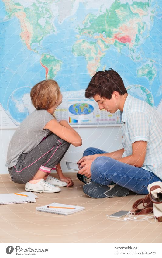 Teenagers sitting by the map in classroom Lifestyle Education School Study Classroom Schoolchild Student Academic studies Cellphone Computer Notebook Tool