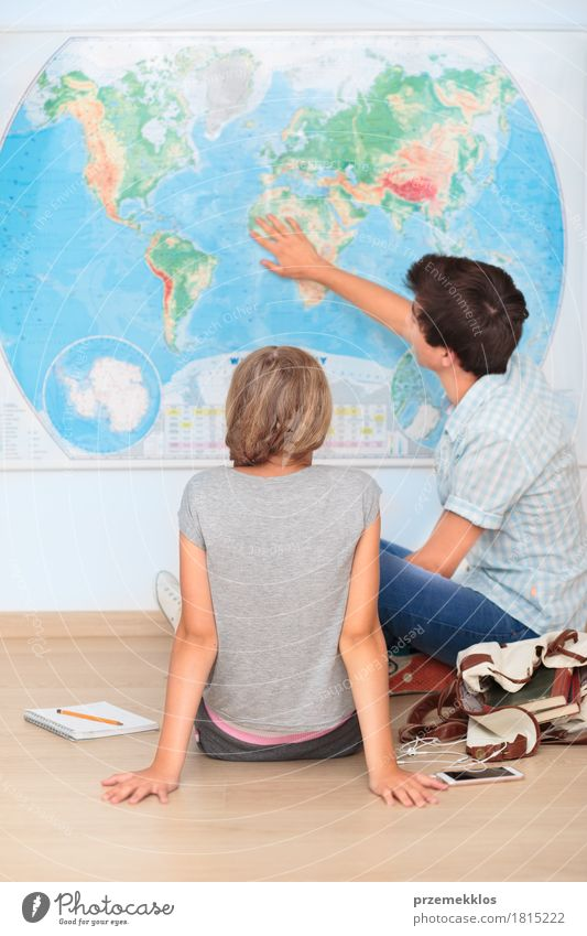Teenagers sitting by the map in classroom Lifestyle Education School Study Classroom Schoolchild Student Academic studies University & College student Cellphone