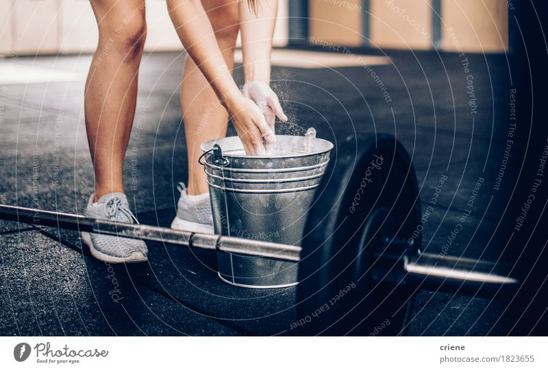 Young woman rubs hands in chalk before lifting barbell Human being Woman Youth (Young adults) Adults Life Lifestyle Sports Leisure and hobbies Copy Space Power