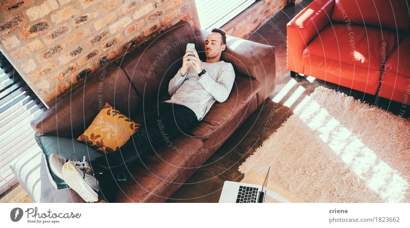 Young adult man laying on couch browsing with his smartphone Human being Youth (Young adults) Young man Relaxation To talk Lifestyle Business Leisure and hobbies Office Modern Technology Telecommunications To enjoy Telephone Couch Internet