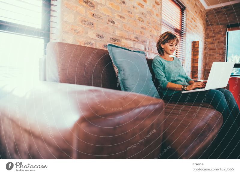 Mature woman sitting on couch at modern home Lifestyle House (Residential Structure) Work and employment Profession Office Business Computer Notebook Technology