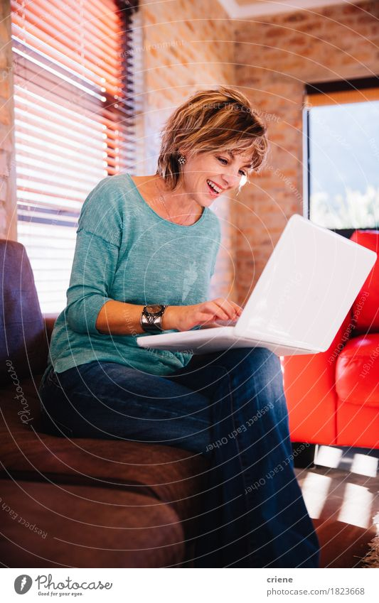 Mature woman video chatting friend with laptop on couch Woman House (Residential Structure) Joy Adults Lifestyle Laughter Business Work and employment