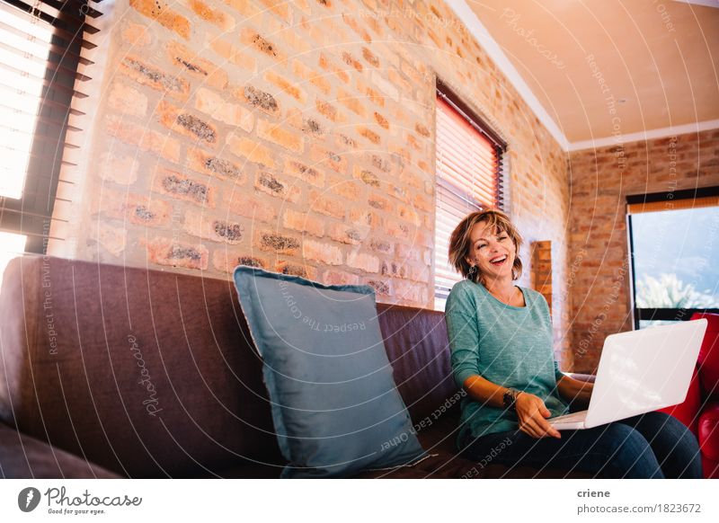 Woman having fun laughing with her laptop on couch at home Human being Joy Adults Senior citizen Lifestyle Laughter Business Work and employment Copy Space
