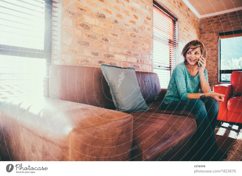 Happy mature woman talking on her smartphone Lifestyle Joy Living room Business To talk Telephone Cellphone PDA Technology Telecommunications Human being Woman