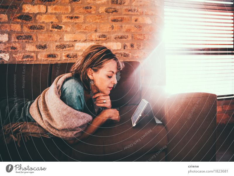 Mature caucasian woman reading newspaper on her digital tablet Woman Relaxation Adults Lifestyle Business Work and employment Leisure and hobbies Modern
