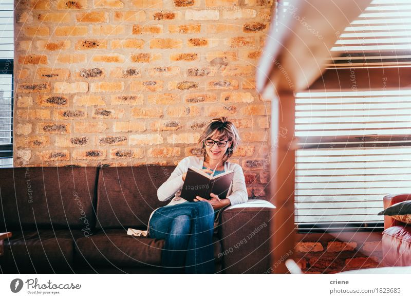 Caucasian woman reading a book in living room in modern house Human being Woman House (Residential Structure) Joy Adults Senior citizen Lifestyle