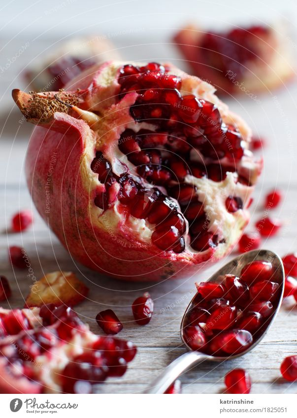 Open fresh ripe pomegranates Red Wood Brown Fruit Nutrition Fresh Delicious Exotic Slice Vegetarian diet Diet Juicy Spoon Tasty Pomegranate