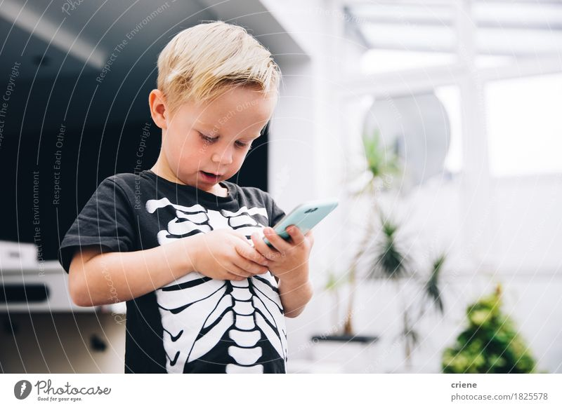 Little boy in skeleton shirt playing games on smart phone Human being Joy Lifestyle Boy (child) Playing Modern Infancy Technology To enjoy Telephone Internet
