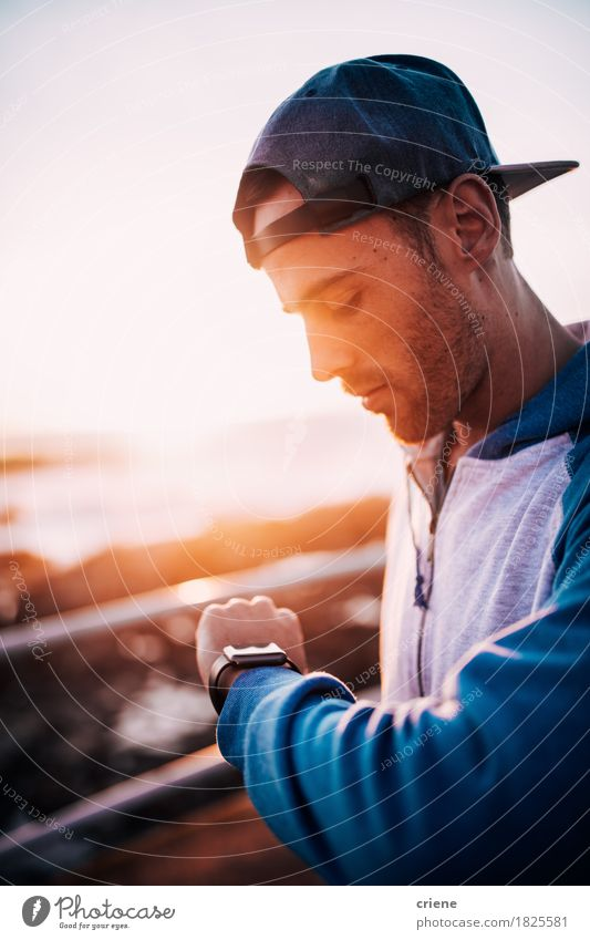 Young caucasian adult man looking on his smart watch at sunset Human being Youth (Young adults) Man Summer Sun Young man Adults Warmth Lifestyle Fashion Modern Technology Observe Internet Cap Email