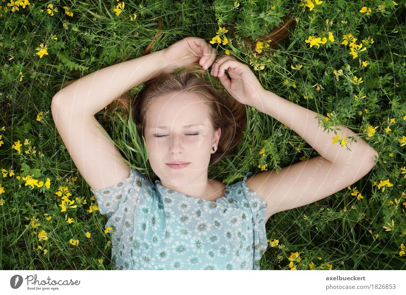 young blonde woman lies with closed eyes on a flower meadow Lifestyle Beautiful Well-being Relaxation Leisure and hobbies Summer Human being Feminine