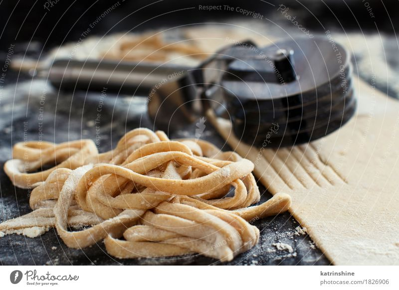 Making homemade taglatelle with a pasta rolling cutter Dough Baked goods Nutrition Italian Food Table Kitchen Tool Make Dark Fresh Tradition Ingredients manual