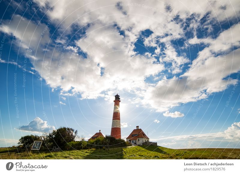lighthouse Sky Clouds Sun Spring Summer Grass Hill House (Residential Structure) Lighthouse Tourist Attraction Large Blue Green Red White Colour photo