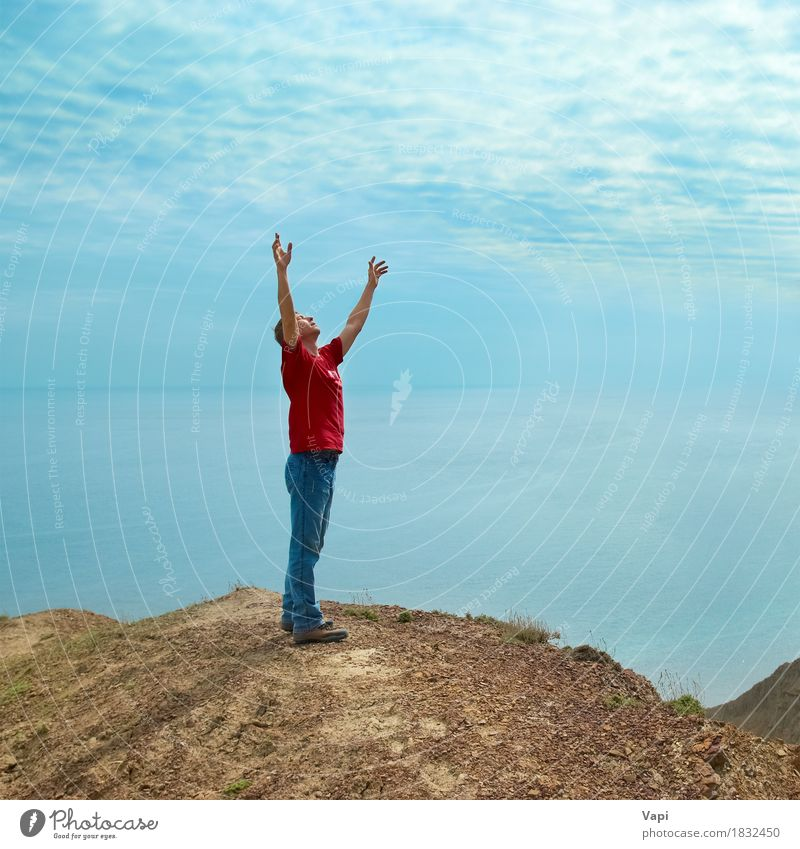 Happy man standing on the cliff Human being Sky Nature Vacation & Travel Youth (Young adults) Man Blue Water Sun Young man Ocean Hand Landscape Red Relaxation