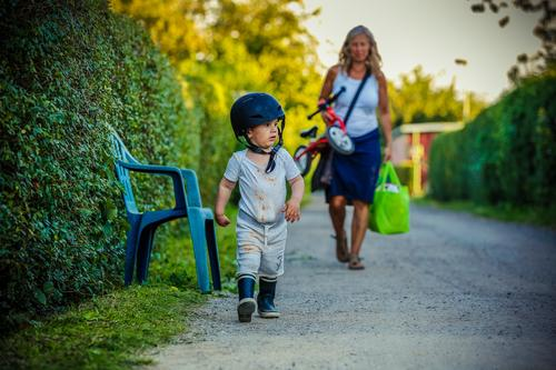 In use Playing Summer Garden Parenting Soldier Child Toddler Woman Adults Family & Relations Environment Nature Rubber boots Helmet Small Determination Safety