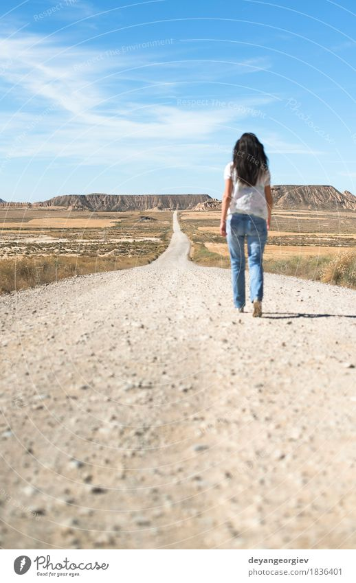 Woman with jeans walking on wild west Vacation & Travel Far-off places Freedom Sun Mountain Girl Adults Earth Sky Horizon Hill Street Lanes & trails Jeans