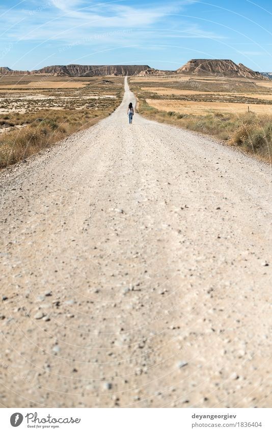 Woman walking on dirt road. Sky Vacation & Travel Sun Eroticism Loneliness Girl Far-off places Mountain Adults Street Lanes & trails Freedom Going Wild Horizon