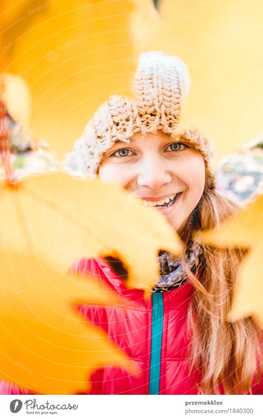 Smiling girl standing behind the blurred yellow autumn leaves Happy Beautiful Garden Girl Youth (Young adults) Face 1 Human being 8 - 13 years Child Infancy