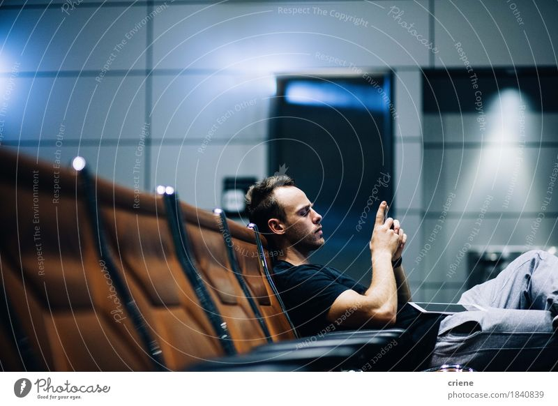 Young male adult waiting in airport lounge browsing smart phone Human being Vacation & Travel Youth (Young adults) Man Young man Adults Lifestyle Tourism Modern Sit Technology Telecommunications Wait Telephone Chair Internet