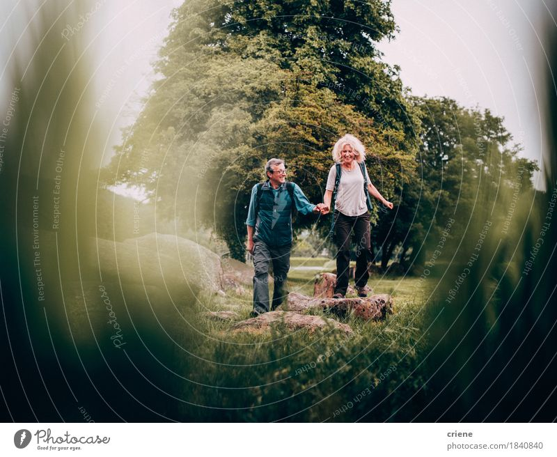 Mature Couple hiking trough beautiful green fields on vacation Human being Woman Nature Vacation & Travel Green Relaxation Joy Adults Senior citizen Lifestyle Sports Couple Leisure and hobbies Hiking Action Smiling