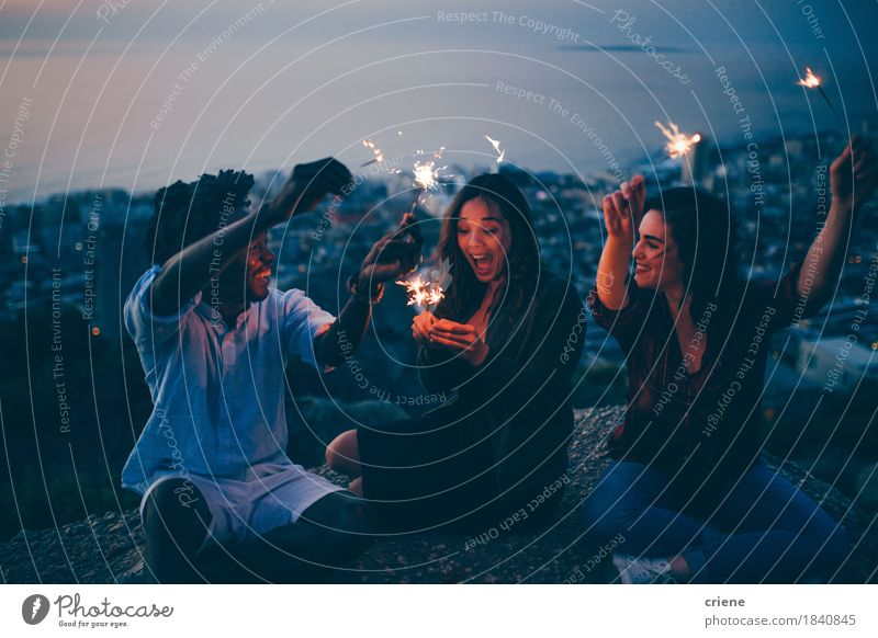 Group of friends celebrating with sparklers at night on rock Human being Youth (Young adults) City Young woman Young man Joy Lifestyle Freedom Feasts & Celebrations Party Group Friendship Birthday Smiling Adventure Summer vacation
