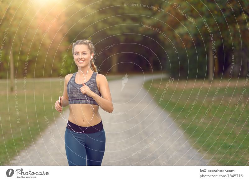 Woman jogging along a country road while listening to music Lifestyle Happy Summer Music Sports Jogging PDA Feminine Adults 1 Human being 18 - 30 years