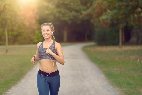 Woman jogging along a country road while listening to music Human being Youth (Young adults) Colour Summer Tree Landscape 18 - 30 years Adults Lanes & trails