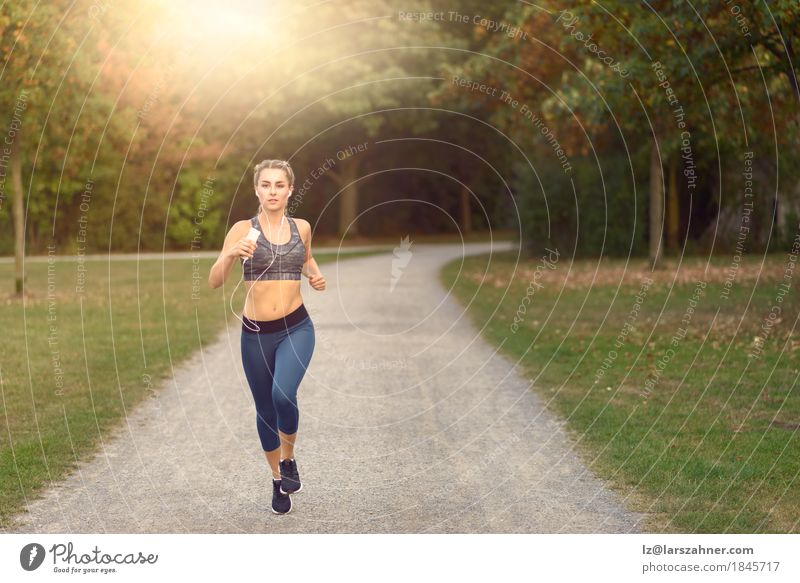 Woman jogging along a country road while listening to music Human being Woman Youth (Young adults) Colour Summer Tree Landscape 18 - 30 years Adults Lanes & trails Lifestyle Movement Sports Feminine Happy Park