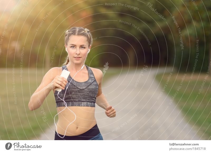 Woman jogging along a country road while listening to music Human being Woman Youth (Young adults) Colour Summer Tree Landscape 18 - 30 years Adults Lanes & trails Lifestyle Movement Sports Feminine Park Fresh