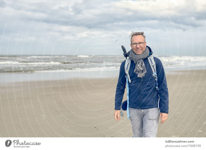 Middle-aged man with glasses walking on the beach Human being Vacation & Travel Man Ocean Clouds Beach Winter Face Adults Autumn Coast Sand Copy Space Waves