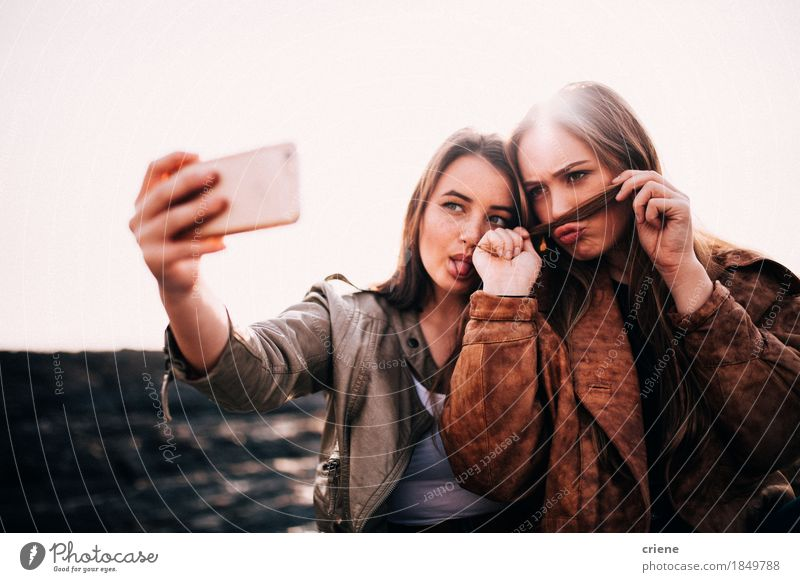 Teenage Girls taking selfies with smart phone on the beach Youth (Young adults) Summer Joy Beach Funny Lifestyle Feminine Happy Couple Together Friendship Technology Smiling Telephone Internet Cellphone