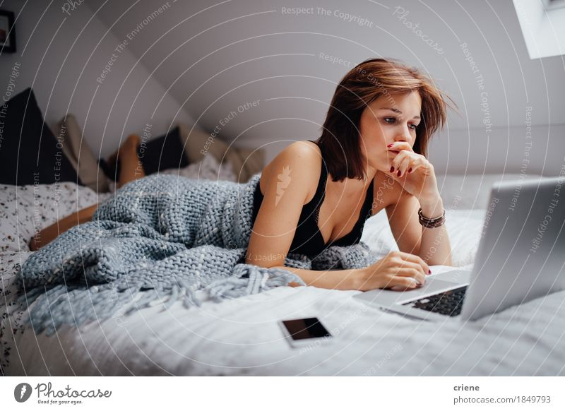 Young female student studying in bed at home with laptop Youth (Young adults) Young woman 18 - 30 years Adults Lifestyle Business Work and employment Flat (apartment) Living or residing Leisure and hobbies Technology Computer Study Academic studies Reading Bed