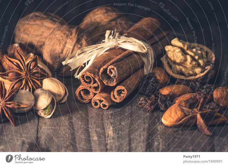 Cinnamon, aniseed, raisins and nuts lie on a rustic wooden table. Christmas spices. Food Fruit Herbs and spices Walnut Star aniseed Pistachio Almond Raisins